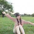 Young woman sitting with arms outstretched in a field - Stockfoto