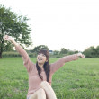 Young woman sitting with arms outstretched in a field - Photo