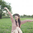 Young woman sitting with arms outstretched in a field - Foto Stock