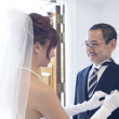 Bride putting handkerchief in her father's pocket - Stock Photo