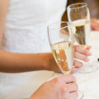Human hands holding champagne flutes - Stock Photo