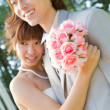 Newlywed couple holding a bouquet - Stock Photo