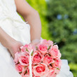 Bride holding a bouquet of pink rose - Stock Photo