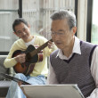 Two senior men enjoying music - Stock Photo