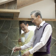 Two senior men cooking food in a kitchen - Photo
