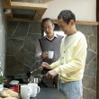 Two senior men cooking food in a kitchen - Stock Photo