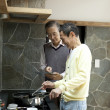 Two senior men using digital tablet while cooking food in a kitchen - Stok fotoğraf