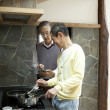 Two senior men using digital tablet while cooking food in a kitchen - Stock Photo