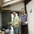Two senior men using digital tablet while cooking food in a kitchen - Foto Stock