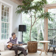 Senior man playing guitar at home - Stock Photo