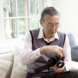 Senior man loading film in a camera - Stock Photo