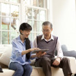 Woman with her father using a digital tablet - Stock Photo