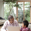 Boy using laptop with his grandfather - Stock Photo
