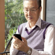 Senior man text messaging on a mobile phone - Photo