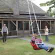 Senior man pushing his grandson on the swing - Stock Photo