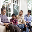 Family sitting on a couch - Stock Photo