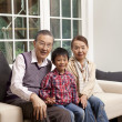 Portrait of a family sitting on a couch - Stock Photo