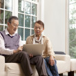 Senior couple sitting on a couch working on a laptop - Stock Photo