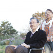 Senior woman pushing her husband in wheelchair — Stock Photo