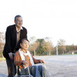 Senior man pushing his wife in wheelchair - Stock Photo