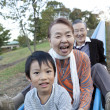 Boy with his grandparents on water slide - Stock Photo