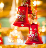 Red Christmas-bell hanging at tree - golden background — Stock Photo