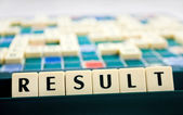 Close up arranged in letter tiles shows the word result — Stock Photo