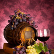 Red wine bottle and wine glass on wodden barrel — Stock Photo