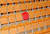 Empty classroom with wood chairs and one red chair — Stockfoto