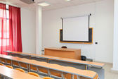 Empty classroom with chairs, desks and chalkboard — Stock Photo