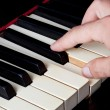 Piano keyboard made of ivory with hands - Stock Photo