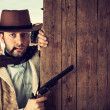 Bad gunman indicates with the gun a wooden plank - Stock Photo