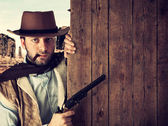 Bad gunman indicates with the gun a wooden plank — Stock Photo
