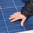 Hand on solar panel - Stock Photo
