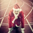 SantClaus in starting position on running track — Stock Photo #33804147