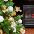 Christmas decorations on a tree with the bottom of a fireplace — Stock Photo
