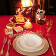 Christmas table near the fireplace, set for a single person. — Stock Photo