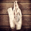 Used ballet shoes hanging on wooden background — Stock Photo