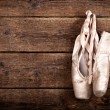 Old used pink ballet shoes hanging — Stock Photo #40171219