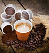 Espresso coffee in disposable cup with pods — Stock Photo