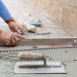Stock Photo: Worker leveling new pavement with specific tool