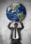 Young businessman sustains the planet Earth — Stock Photo
