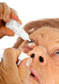Elderly woman applying eye drops — Foto Stock