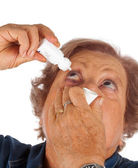 Elderly woman applying eye drops — 图库照片