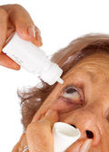 Elderly woman applying eye drops — Stok fotoğraf