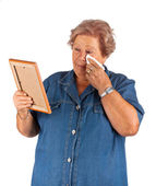 Old lady crying watching a blank photo frame — Stock Photo