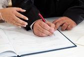 Nevěsta a ženich podepisování oddací list — Stock fotografie