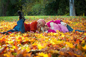 Happy smiling children lying on autumn leaves — Stock Photo