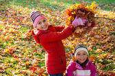 Happy smiling children play with autumn leaves — Stock Photo