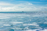 Icy landscape with lighthouse on a pier — Stock fotografie